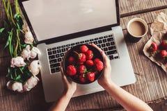 L'espace de travail avec des mains du ` s de fille, l'ordinateur portable, bouquet des pivoines fleurit, café, les fraises, smart Photographie stock