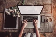 L'espace de travail avec des mains du ` s de fille, l'ordinateur portable, bouquet des pivoines fleurit, café, les fraises, smart photo libre de droits