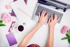L'espace de travail avec des mains du ` s de fille sur le clavier, le carnet, les verres, la tasse de café et la glycine d'ordina Photos libres de droits