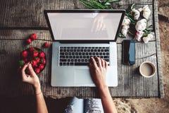 L'espace de travail avec des mains du ` s de gir, l'ordinateur portable, bouquet des pivoines fleurit, café, les fraises, smartph Photographie stock
