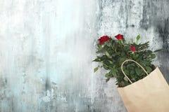 L'espace de travail avec la rose de rouge fleurit dans un sac de papier Photo libre de droits