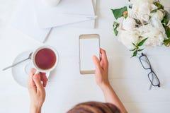 L'espace de travail avec le ` s de fille remet tenir le téléphone intelligent avec l'écran vide et la tasse de thé, verres, carne Photos stock