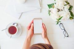 L'espace de travail avec le ` s de fille remet tenir le téléphone intelligent avec l'écran vide, tasse de thé, verres, carnets, l Photographie stock