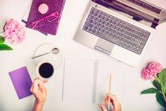 L'espace de travail avec l'ordinateur portable, le ` s de fille remet l'écriture en carnet, verres, tasse de café et fleurs de gl Image libre de droits