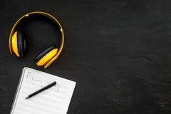 L'espace de travail du compositeur ou le DJ avec des écouteurs et des notes noircissent la maquette de vue supérieure de fond Image stock