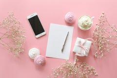 L'espace de travail féminin de bureau dans les couleurs blanches et roses avec le petit s-souffle de ` de bébé fleurit le gypsoph Photographie stock