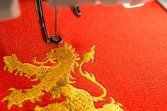 L'espace de travail de machine de broderie et le lion d'or conçoivent sur le tissu rouge Photographie stock libre de droits