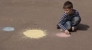 L'espace et planètes de dessin de garçon sur le trottoir Photo stock