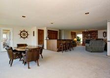 L'espace ouvert dans la maison de luxe Salle à manger avec la table brune mise et le salon avec la cheminée de brique Photographie stock