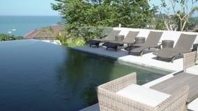 L'espace piscine de natation de bord de luxe récréationnel d'infini avec des lits pliants et la vue de mer banque de vidéos