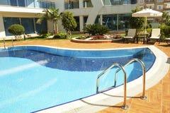 L'espace piscine de natation du nouveau complexe résidentiel de luxe avec des tuiles, des poignées d'escaliers de chrome et des d photos libres de droits