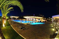 L'espace piscine de station de vacances allumé la nuit Image stock