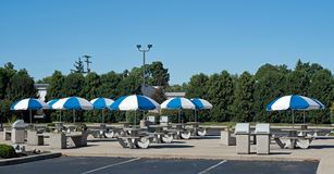 L'espace restauration extérieur vide avec les parapluies bleus et blancs photos stock