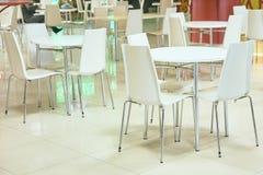 L'espace restauration Tables et présidences blanches intérieur lumineux Image stock