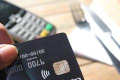 L'espace sans contact de copie de fond de pdq de carte de paiement avec la main tenant la carte de crédit pour payer Photographie stock