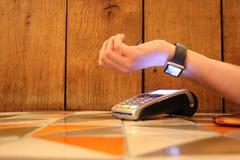 L'espace sans contact de copie de fond de pdq de montre de pomme de paiement avec la main tenant la carte de crédit pour payer Photographie stock
