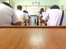 L'espace sur la table pour le texte de salutation et objet avec le fond de salle de classe de tache floue Images libres de droits