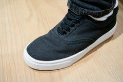 L'espadrille noire de toile sous le chargement initial a coupé des jeans Photographie stock libre de droits