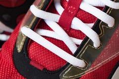 L'espadrille rouge de la jeunesse avec le blanc a délié les dentelles Photos libres de droits