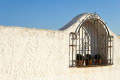 L'Espagnol typique a râpé la fenêtre dans une maison blanche de murs Image libre de droits