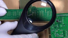 L'esperto in elaborazione elettronica esamina il modulo di memoria di RAM con la lente d'ingrandimento stock footage