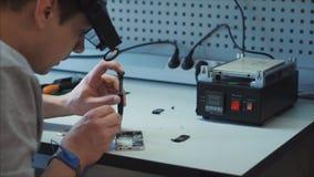 L'esperto elettronico nel primo piano identifica la causa del guasto all'aggeggio video d archivio