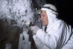 L'esploratore della caverna esamina le stalagmite ghiacciate immagine stock