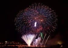 L'esplosione dei fuochi d'artificio di Colorfull nel cielo scuro dalla parte di sinistra con il silouthe del villaggio sul fondo, Fotografie Stock