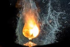L'esplosione di vino in un vetro, molta spruzza e spezzetta, il danno dell'alcool fotografia stock