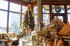 L'esposizione dei piatti appoggia ecc in donna pionieristica mercantile davanti all'albero di Natale vago ed in finestre che most fotografie stock libere da diritti