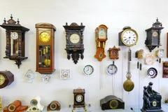 L'esposizione del museo degli orologi delle dimensioni, del materiale e dell'ingranaggio differenti contro una parete bianca Immagini Stock Libere da Diritti