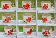 L'esposizione di molti mugss del caffè sugli scaffali di legno bianchi ingarden. Immagini Stock Libere da Diritti
