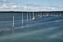L'esposizione lunga dell'laghi puntella un giorno tempestoso, creante un'acqua confusa con i pali che escono dalla ritenzione di  fotografia stock libera da diritti