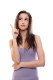 L'esposizione della donna del brunette qualcosa ed osserva in su Immagine Stock Libera da Diritti