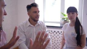 L'esprit d'équipe, les gens s'asseyant sur des chaises en cercle donnent cinq ensemble sur la session de thérapie de groupe banque de vidéos