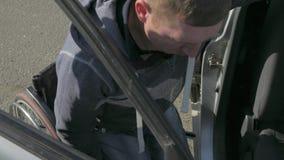 L'essai d'estropié obtiennent dans la voiture, homme handicapé dans le fauteuil roulant, montrant des problèmes considérés par de banque de vidéos