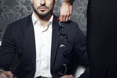 L'essai sexy de femme séduisent l'homme d'affaires riche sur le sofa photos libres de droits