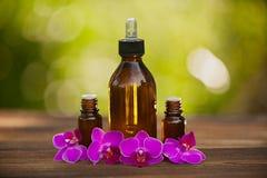 L'essenza dell'orchidea fiorisce sulla tavola in bello barattolo di vetro Fotografia Stock