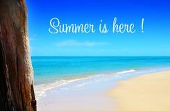 L'estate è qui testo sopra l'ampia spiaggia sabbiosa con i cieli blu Fotografie Stock