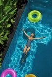 L'estate si distende Donna che galleggia, acqua della piscina Festa di estate fotografia stock libera da diritti