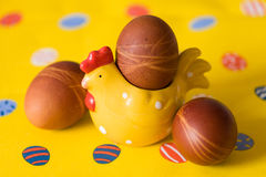 L'estere organico naturale eggs con la decorazione della gallina ed il fondo giallo Preparazioni per Pasqua Fotografie Stock