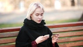 L'esterno biondo felice della ragazza realizza la transazione questa carta di debito-credito di pagamento dell'oro allo smartphon stock footage