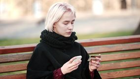 L'esterno biondo triste della ragazza esegue la carta di debito-credito di pagamento dell'oro di transazioni allo smartphone archivi video