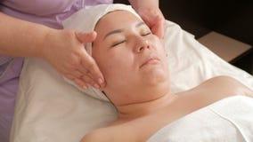 L'estetista conduce la donna asiatica di massaggio facciale terapeutico Primo piano delle mani e del viso femminili in un centro