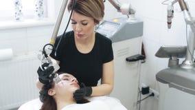 L'estetista del movimento lento fa la sbucciatura facciale del laser per la donna con il dispositivo speciale video d archivio
