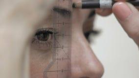 L'estetista del primo piano fa la marcatura del sopracciglio con il cliente della matita per la correzione del sopracciglio stock footage