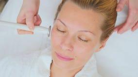 L'estetista fa il massaggio del facial di ultrasuono video d archivio