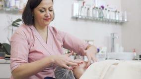 L'estetista fa il massaggio facciale nella clinica di bellezza stock footage