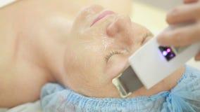 L'estetista fa il Rf-sollevamento alla giovane donna Procedure cosmetiche per il fronte video d archivio