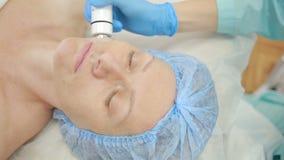 L'estetista fa il Rf-sollevamento alla giovane donna Procedure cosmetiche per il fronte archivi video